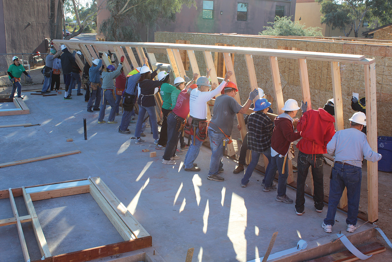 Volunteers help raise the walls on a Habitat home