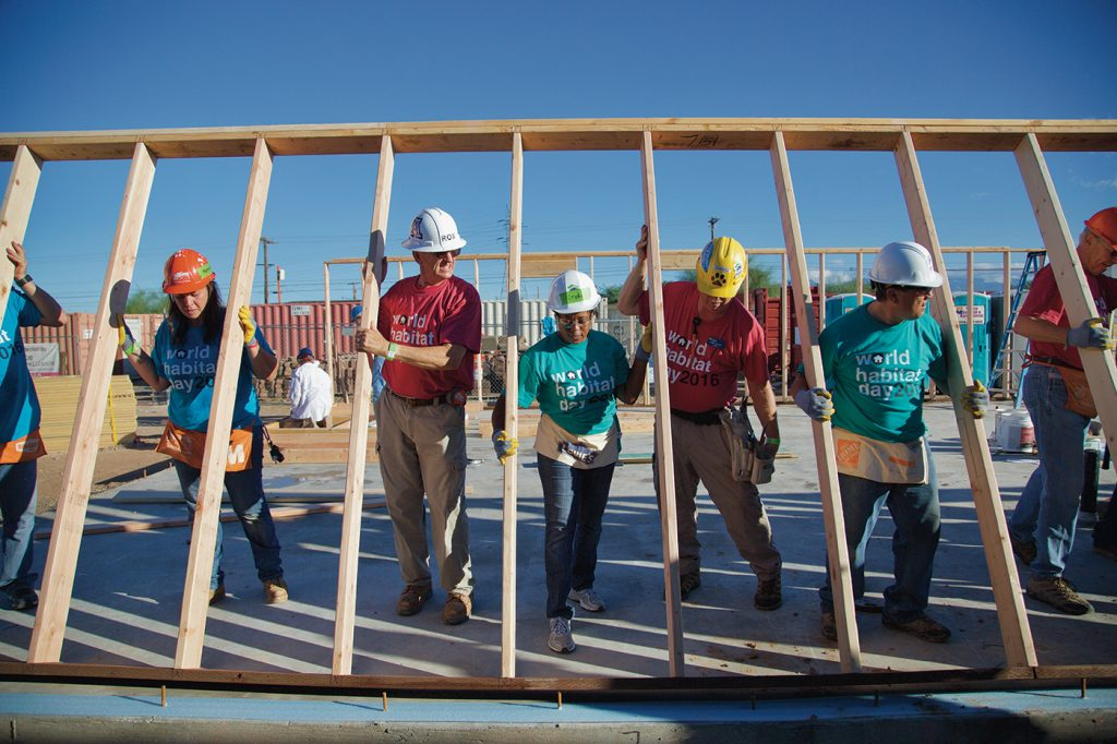 Volunteer raising the walls of a habitat home